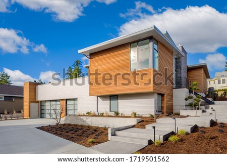 Beautiful modern home exterior with three car garage on bright sunny day with blue sky and clouds