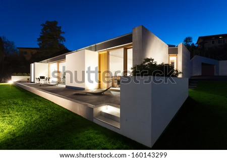 beautiful modern house in cement, view from the garden, night scene #160143299