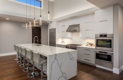 Beautiful Modern Kitchen In New Luxury Home. Features Large Waterfall Island with Double Ovens and Hardwood Floors