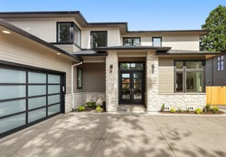 Beautiful modern luxury home exterior on bright sunny day with blue sky. Features columns flanking entrance and modern garage door with panels.
