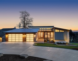 Beautiful modern style luxury home exterior at sunset. Features three car translucent garage with clerestory windows and beautiful sunset colors.