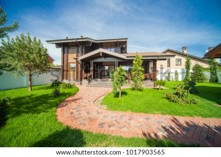 Beautiful modern wooden house with stained glass windows, view from the green lawn. #1017903565