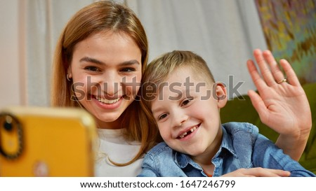 Beautiful mom and son making selfie at home. Happy family having a facetime video call. Unity, connection, technology concept