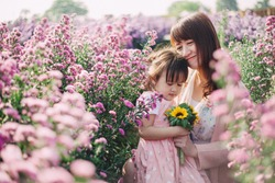 Beautiful moment and romantic love emotional picture of mother and her little kids playing together in the flowers garden. Concept for happy family bonding and spring or summer season.