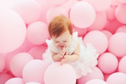 beautiful, 11 month baby girl standing among pastel pink balloons
