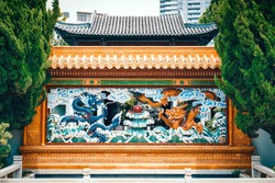 Beautiful monument of two dragons chasing the sun in front of a traditional Chinese building. Chinese garden of friendship, Sydney, Australia.