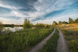 Beautiful moody high resolution colorful and dramatic wide anlge shot of a spring landscape with meadow, trees, lake, hill, countryside path, road and a nice blue sky with white clouds