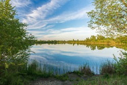 Beautiful moody high resolution colorful and dramatic wide anlge shot of a spring landscape with lake, trees, canes, countryside and a nice blue sky with white clouds reflexting in the water