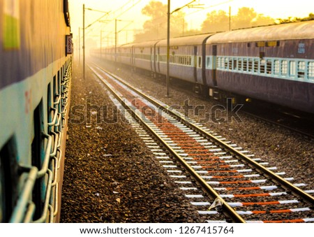 beautiful morning image of two Indian train with rail between them in yellowish morning light and a bit fogg. Perfect to show Indian railways system in news or article