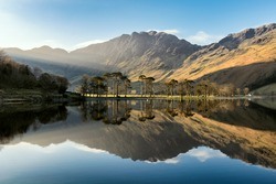 Beautiful morning sunlight shining on Buttermere in the Lake District with mirror like reflections.