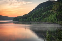 Beautiful Morning Sunrise on a Steamy Lake Surrounded by Mountains With Trees in Quebec Canada