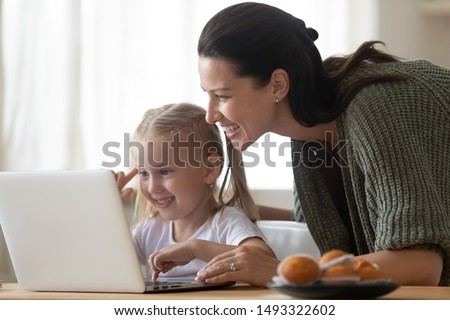 Beautiful mother and child looks at laptop screen spend time in kitchen using app education program, choose cartoons, teach kid pc usage, controls what daughter watching on internet cyberspace concept