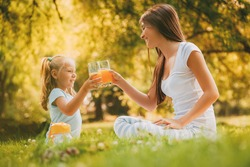 Beautiful Mother and daughter at the park having little picnic. They are enjoying and drinking orange juice.