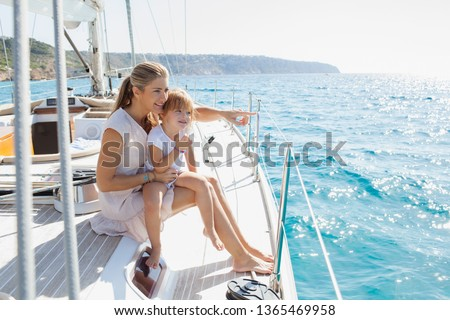 Beautiful mother and daughter child together on private luxury sailing yacht, pointing smiling outdoors. Family activities summer vacation at sea, travel transportation leisure recreation lifestyle. #1365469958