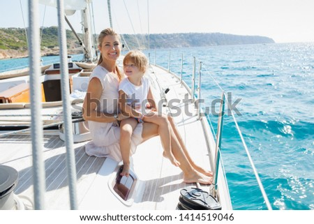 Beautiful mother and daughter enjoying summer holiday luxury sailing yacht trip, smiling in sunny exterior. Family relaxing day out, adventure travel at sea, leisure recreation aspirational lifestyle. #1414519046