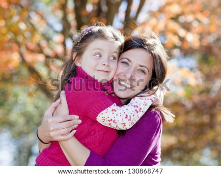 Beautiful mother and daughter hugging against fall background