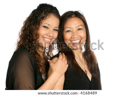 Beautiful mother and daughter of Thai origin, in formal black dress, shot on white background.