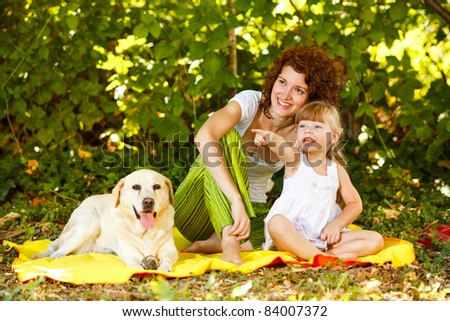 Beautiful mother and daughter relaxing in nature with their dog