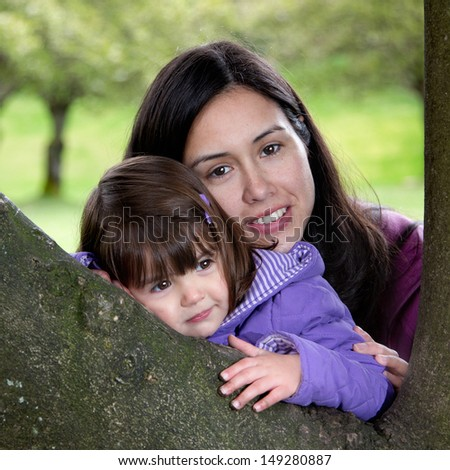 Beautiful Mother and Daughter Resting on a Tree as they Enjoy Nature