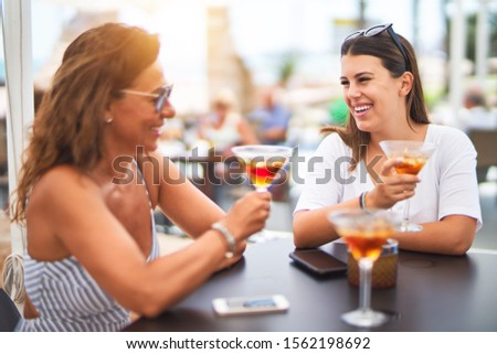 Beautiful mother and daugther sitting at terrace of restaurtant drinking cocktail speaking and smiling #1562198692