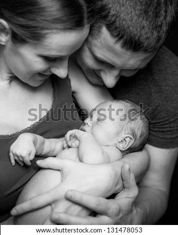 Beautiful mother and father smiling holding their newborn baby boy