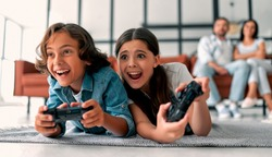 Beautiful mother and handsome father with their daughter and son spending time together at home. Children are playing video games. Happy family concept.
