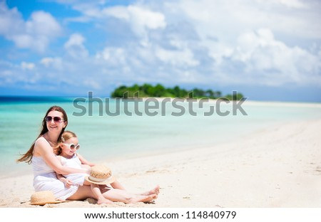 Beautiful mother and her adorable little daughter at tropical beach
