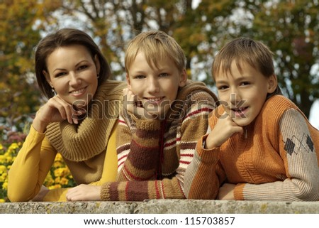 beautiful mother and her children on autumn background