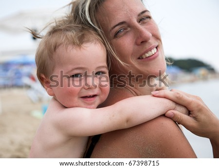 Beautiful mother and her son play together at the beach