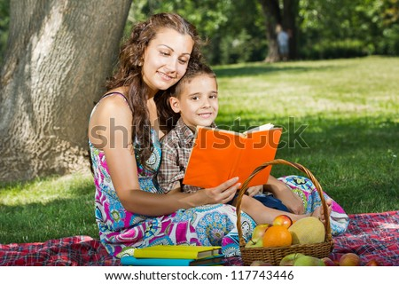 beautiful mother and little boy reading book together - stock photo