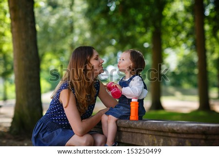 Beautiful mother and little daughter blowing soap bubbles together in summer park