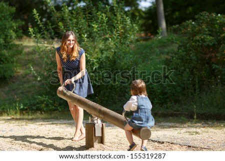 Beautiful mother and little daughter having fun together on playground - stock photo