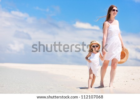 Beautiful mother and little daughter on tropical beach vacation