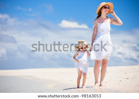 Beautiful mother and little daughter walking along tropical beach