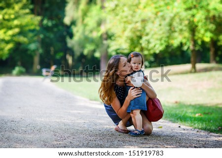 Beautiful mother and little daughter walking together in summer park - stock photo