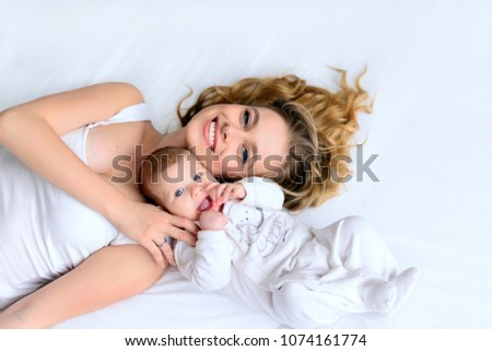 Beautiful mother and newborn baby lying in bed, hugging with love, smiling. Pretty blonde woman and happy infant lay together on white backgound of bed. From high angle shot, above view.