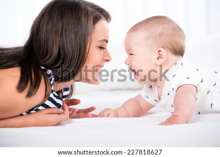 Beautiful mother and son are lying in bed and looking at each other.