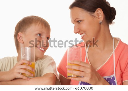 beautiful mother and son drink juice on a white