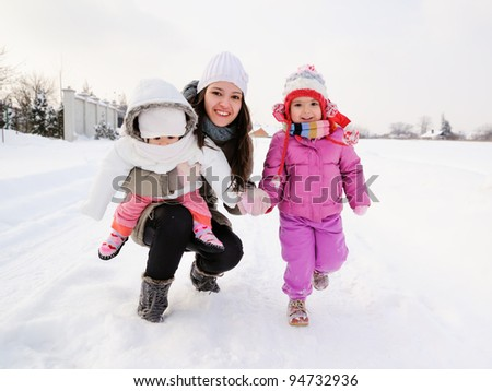 Beautiful mother and two daughters enjoying winter outdoors. They are smiling and playful in the snow.