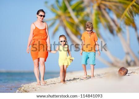 Beautiful mother and two kids enjoying beach vacation - stock photo