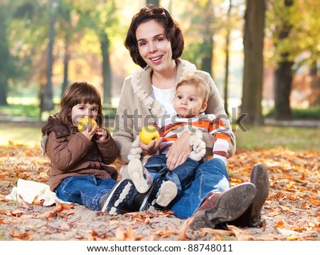 Beautiful mother embracing her little children in a autumn park