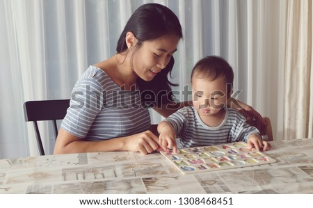 Beautiful mother is having a beautiful time with her cute son. Lovely little boy is learning alphabets A-Z with his beautiful mother. Vintage photo mom and son.