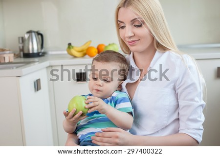 Beautiful mother is holding her child on her knees. She is looking at him and smiling. The boy is holding an apple and looking at it with interest. Copy space in left side