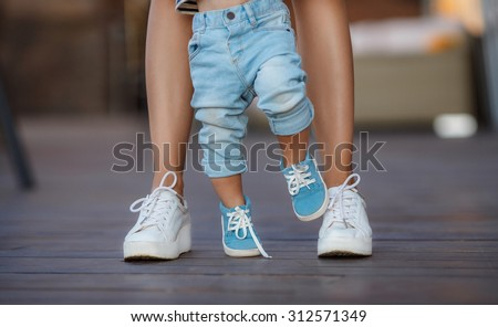 Shutterstock beautiful mother is walking on the pier with her little baby boy son with first steps. feet of mother and child