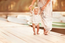 beautiful mother is walking on the pier with her little baby girl daughter with first steps