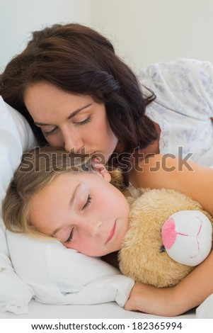 Beautiful mother kissing sleeping daughter in bed at home