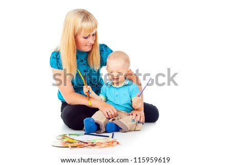 beautiful mother with a child draw with pencils