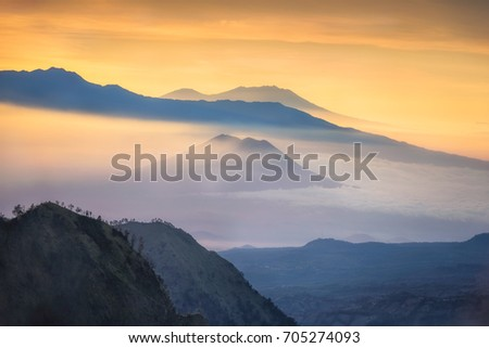 Beautiful mountain and sea of clouds view during sunrise from viewpoint at Bromo Tengger Semeru National Park, East Java, Indonesia. #705274093