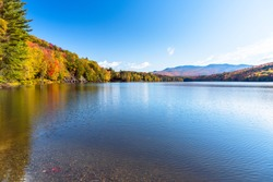 Beautiful mountain lake surrounded by deciduous trees at the peak of fall foliage on a sunny morning. Reflection in water.
