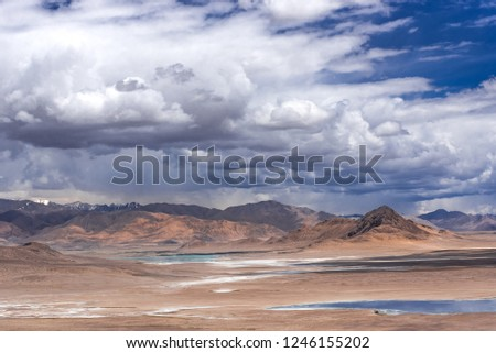 Beautiful mountain landscape against the backdrop of a stormy sky. Thunder Sky. Azure lake in the desert. #1246155202